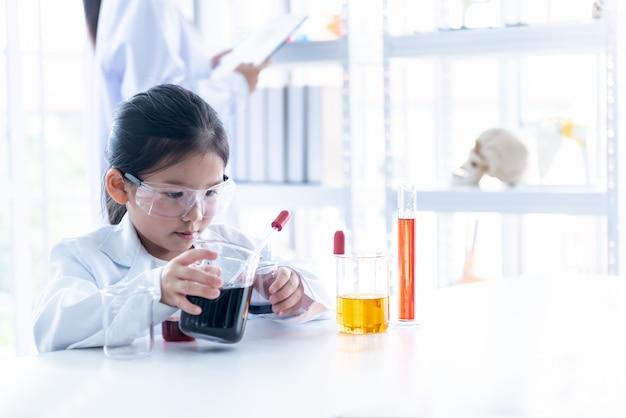 Азиатская девушка learning and провела научный эксперимент на белом столе