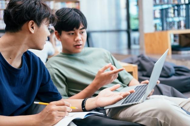 学習、教育、学校のコンセプト。テストや試験のために勉強している若い女性と男性。友達と一緒に家庭教師の本。若い学生のキャンパスは、友人が追いついて学習するのを助けます。