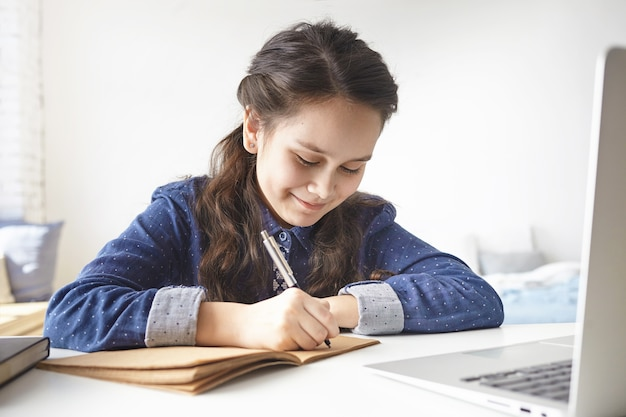 학습, 교육, 여가, 취미 및 현대 기술. 명랑 긍정적 인 십 대 소녀는 그녀의 방에 책상에 앉아 그녀의 일기에 메모를 만들고