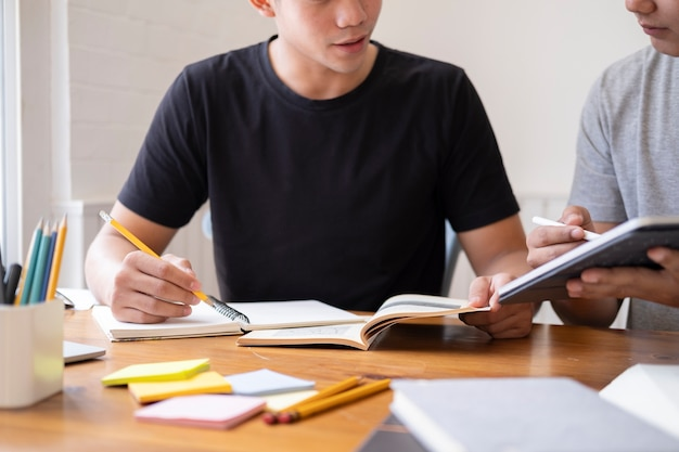Learning, education and school concept. young woman and man studying for a test or an exam. tutor books with friends. young students campus helps friend catching up and learning.