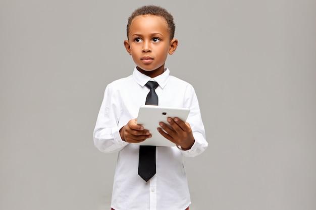 학습, 교육, 기술 및 커뮤니케이션 개념. 무선 인터넷 연결을 사용하여 디지털 터치 패드 태블릿으로 포즈를 취하는 교복에 잘 생긴 스마트 아프리카 학생