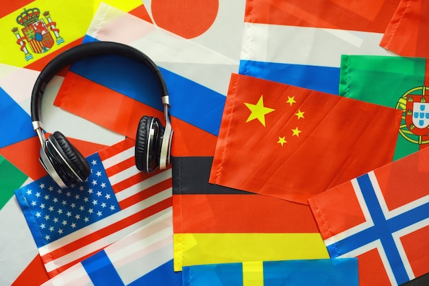 Learning foreign languages. audio language courses. background from countries flags and headphones on the table.