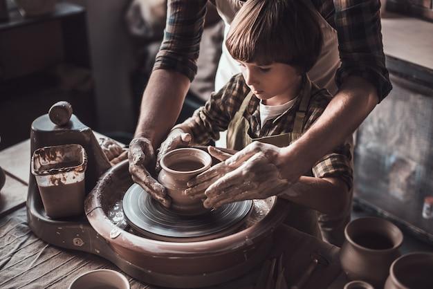Учимся у уверенного гончара. крупный план уверенного в себе маленького мальчика, делающего керамический горшок на уроке гончарного дела