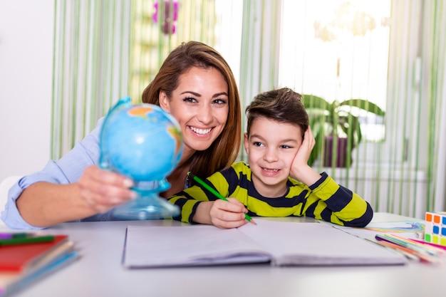 家から学ぶ、ホームスクールの子供のコンセプト。母親の助けを借りてオンライン学習で小さな男の子の研究。