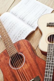 Учимся играть на гитаре. вертикальные крупным планом фото акустических гитар и укулеле, лежащих на деревянном полу с нотами. вид сверху. музыкальное оборудование. музыкальный магазин. музыкальные инструменты