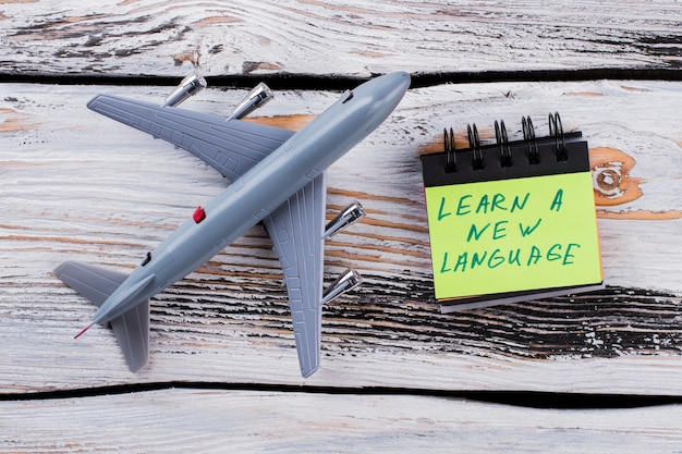Learning new language and traveling concept. top view toy plane on white wooden table.