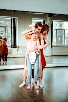 新しい動きを学ぶ。赤毛の若いダンス教師と彼女の生徒たちは、新しいダンスの動きを学びながら集中しているように見えます