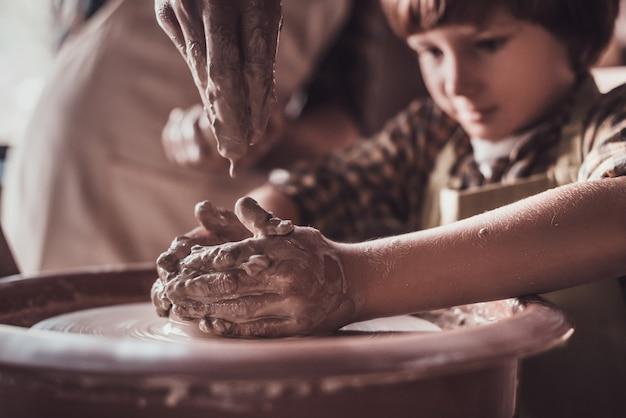 Изучение нового навыка. крупный план уверенного в себе маленького мальчика, делающего керамический горшок на уроке гончарного дела