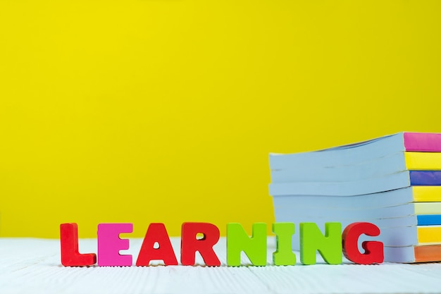 Learning text alphabet and pile of book with yellow background.