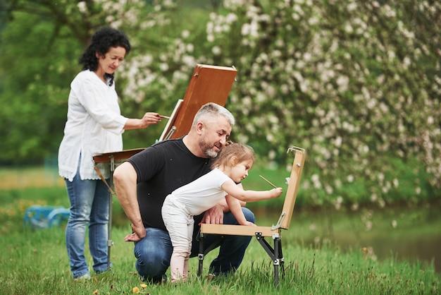 Изучая это искусство. бабушка и дедушка веселятся на природе с внучкой. концепция живописи