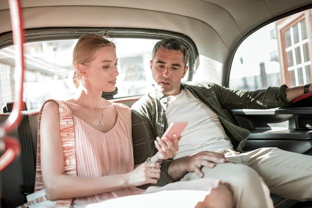 방법을 배우십시오. 그녀의 집중된 남편에게 차 안에 그와 함께 앉아 있는 그녀의 스마트폰에 그들의 경로를 보여주는 웃는 여자.