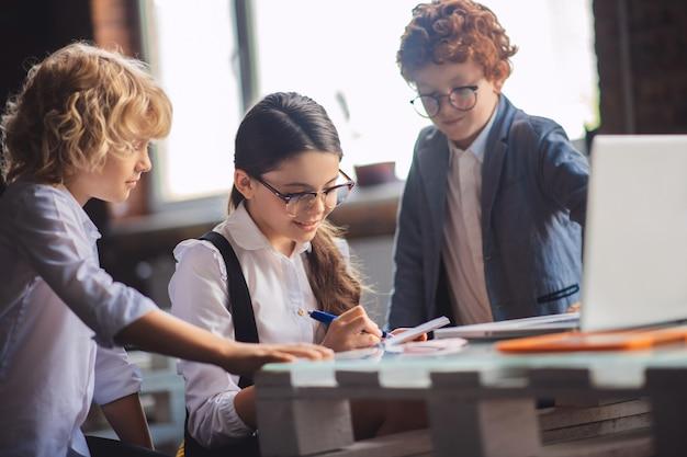 Обучение. трое симпатичных детей вместе работают над уроками и выглядят вовлеченными