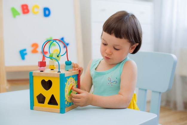 Learning time of a child with a wooden clock at the children's table in the room
