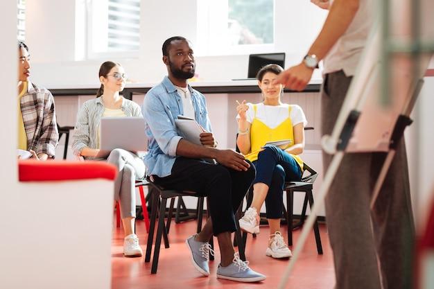 함께 배우기. 편안하게 앉아 선생님의 말을 들으면서 선생님을 바라 보는 차분한 세심한 젊은이들