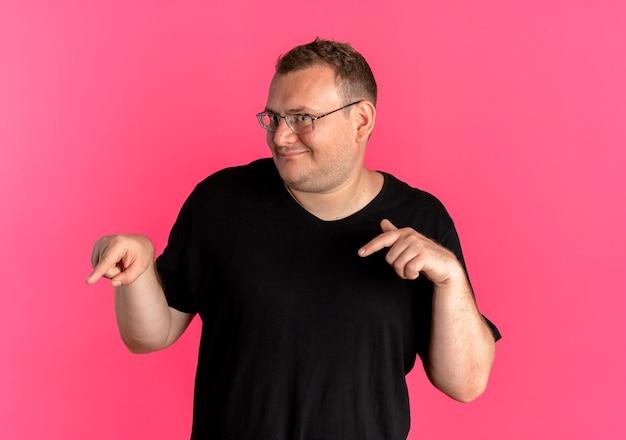 Uomo in sovrappeso in leasing con gli occhiali che indossa una maglietta nera con le dita indice giù sopra il rosa