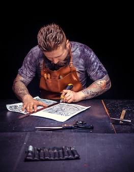 Leather artisan создает новое изделие из кожи на рабочем месте