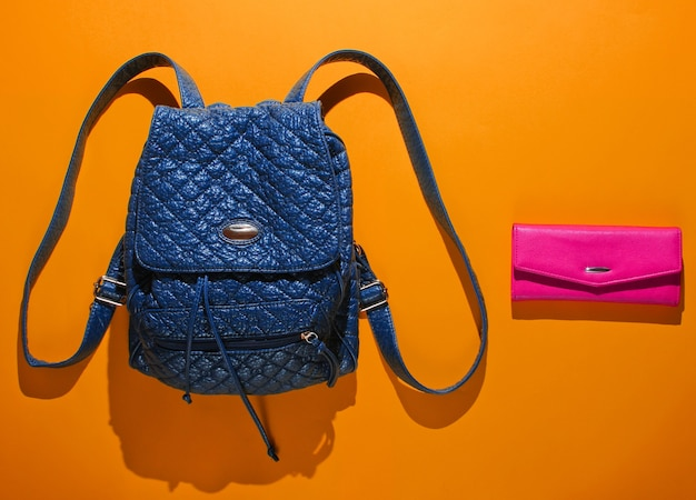 オレンジ色の背景にストラップとピンクの財布が付いた革のバックパック。トップビュー、ミニマリズムファッション