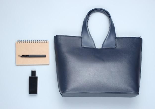 革のバッグ、ノートブック、灰色のテーブルに香水のボトル。ビジネスとファッションのアクセサリー。トップビュー、ミニマリズム