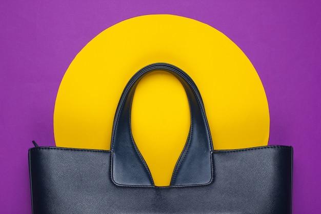 Кожаная сумка на фиолетовой бумаге с желтыми геометрическими фигурами.