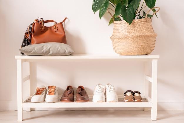베개와 바구니에 가죽 가방, 상단 선반에 녹색 국내 식물이 있고 하단 선반에는 낚시를 좋아하는 캐주얼 신발 행