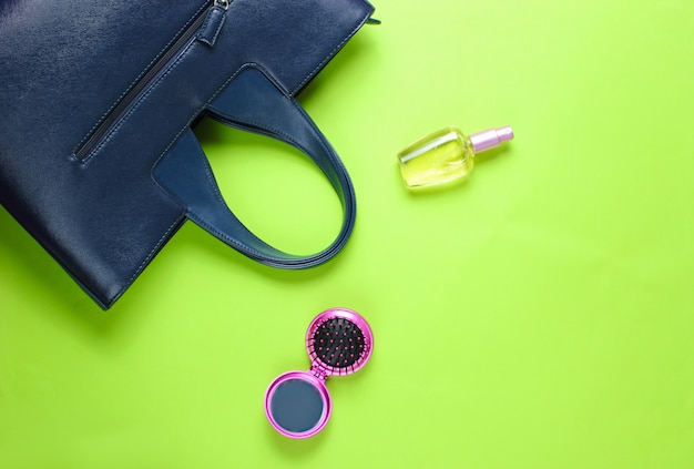 Leather bag, perfume bottle, comb-mirror on green paper background