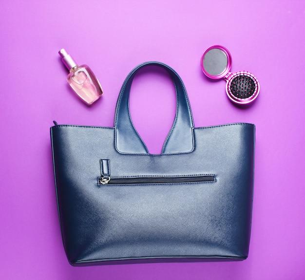 Кожаная сумка, флакон духов, расческа-зеркало на фиолетовом бумажном фоне