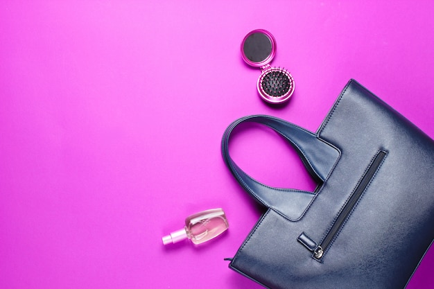 Leather bag, perfume bottle, comb-mirror on pink paper background