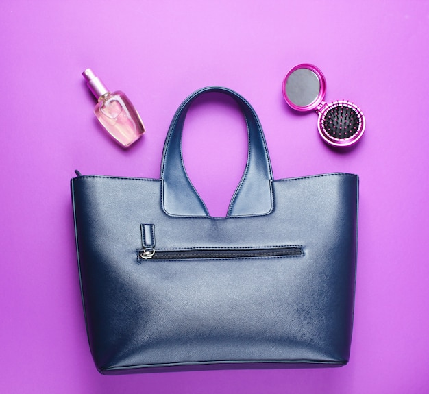 Leather bag, perfume bottle, comb-mirror on purple paper background