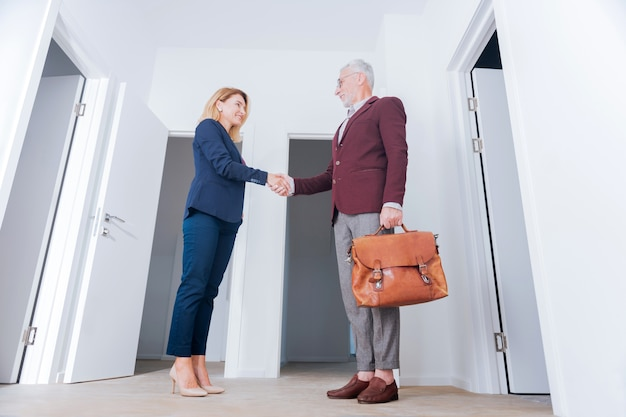 Leather bag. stylish bearded businessman holding brown leather bag shaking hand of his beautiful beaming partner