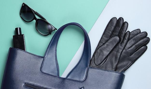 革のバッグ、サングラス、手袋、グレーブルーの背景に香水瓶。女性のファッションアクセサリー