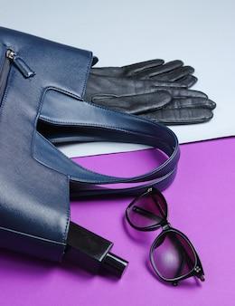 グレーパープルのテーブルにレザーバッグ、サングラス、手袋、香水瓶。レディースファッションアクセサリー