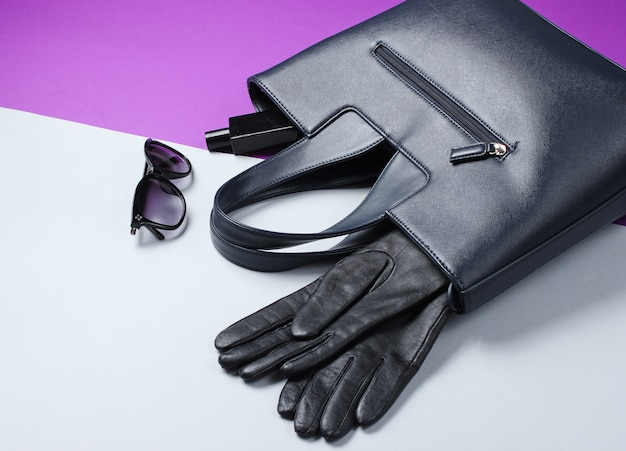 Кожаная сумка, солнцезащитные очки, перчатки, флакончик духов на серо-фиолетовом столе. модные женские аксессуары