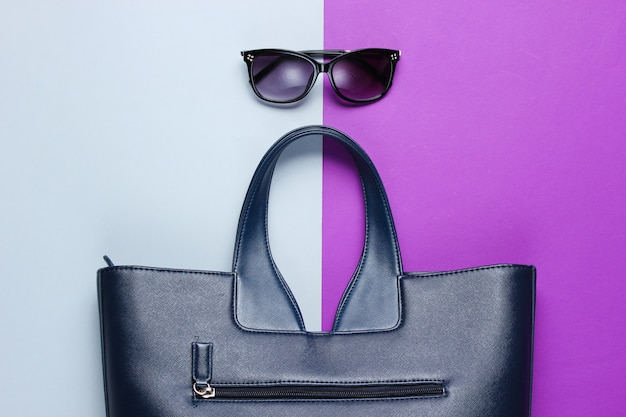 Leather bag, sunglasses on gray-purple table. top view