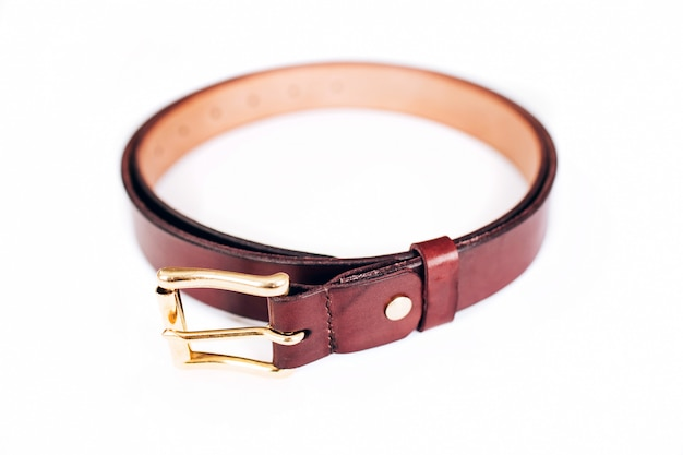 Leather belt on a white background. belt is twisted in a circle. gold hardware.