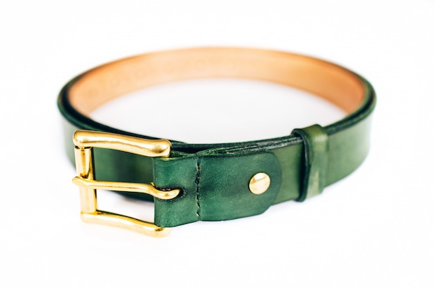 Leather belt on a white. belt is twisted in a circle. gold hardware.