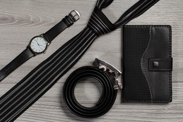 금속 버클이 있는 가죽 벨트, 가죽 스트랩이 있는 시계, 실크 넥타이, 회색 나무 배경에 가죽 커버가 있는 노트북