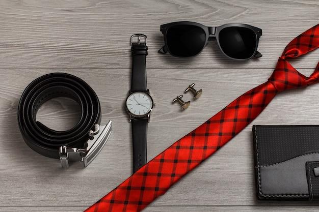 금속 버클이 있는 가죽 벨트, 가죽 스트랩이 있는 시계, 선글라스, 빨간색 실크 넥타이, 커프스 단추, 회색 나무 배경에 가죽 덮개가 있는 노트북