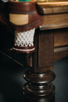 Leather billiard hole and table leg in a billiard club.