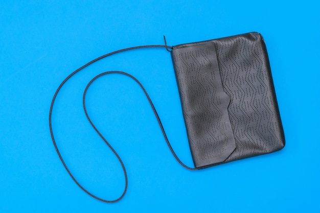 Leather black women bag on blue background. the view from the top. flat lay.