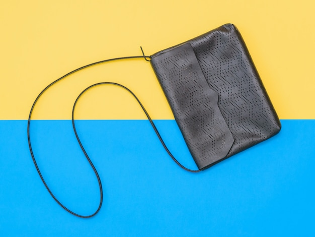 Leather black women bag on yellow and blue background. the view from the top. flat lay.