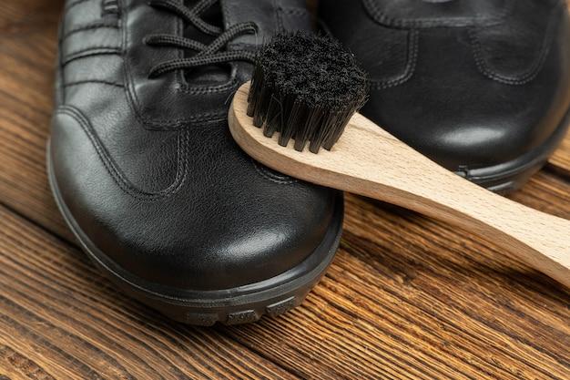 革のブーツ、靴磨き用のブラシ、木製の背景の靴ケア製品