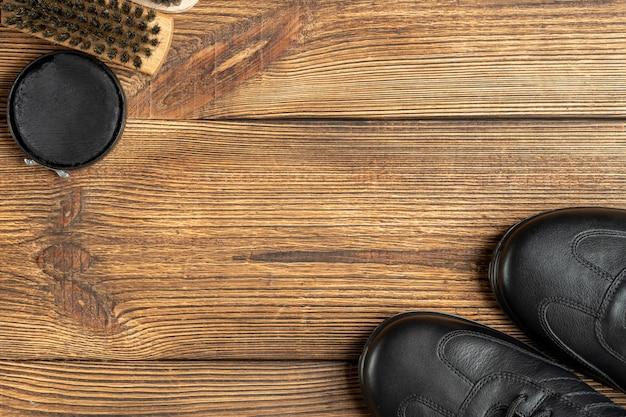 革のブーツ、ブラシ、靴磨きワックス、コピースペースのある木製の背景の靴ケア製品