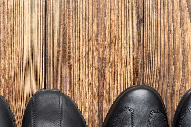 コピースペースと木製の背景に革のブーツ、靴、靴