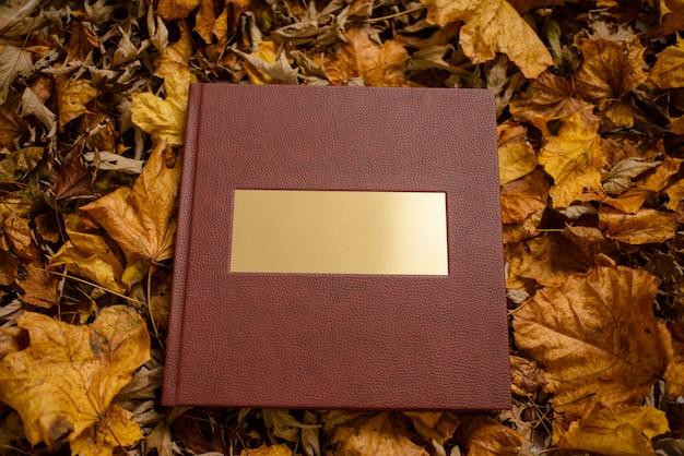 茶色の葉が付いている金の銘板が付いている革茶色の本。テキストのための場所。