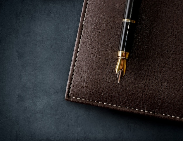 Leather brown notebook with fountain pen. business background.