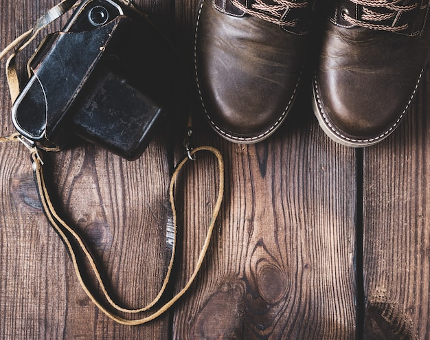 Leather brown shoes and an old vintage camera