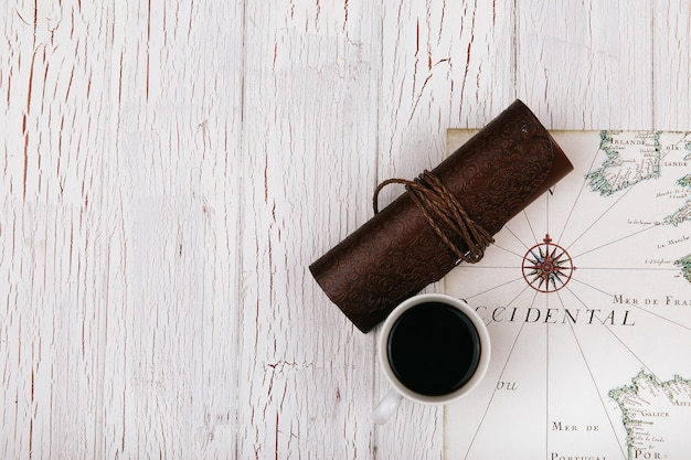 Leather case and cup of coffee stand on white travel map