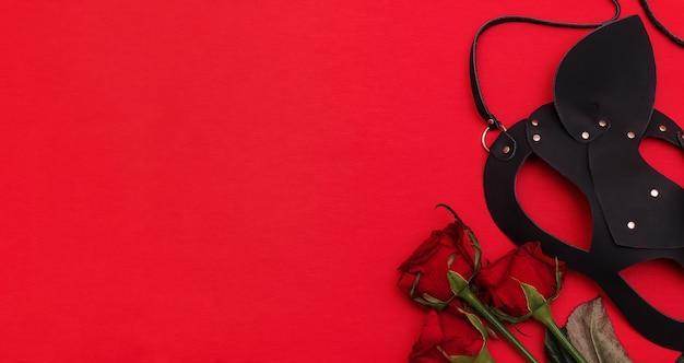 Кожаная маска кошки и букет роз. концепция дня святого валентина, бдсм-сообщества.