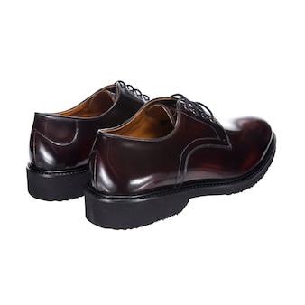 白い表面に分離された、磨かれた革から茶色の靴ひも付きの革の古典的なメンズシューズ