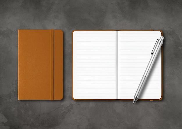 ペンで裏打ちされた革製の閉じたノートと開いたノート。暗いコンクリートの背景に分離されたモックアップ
